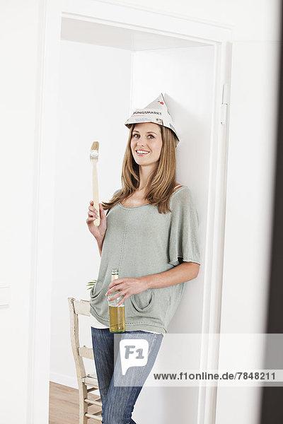 Porträt einer Frau mit Bierflasche und Pinsel  lächelnd