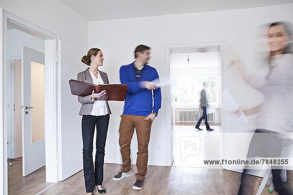Ehepaar  das einen Vertrag mit dem Immobilienmakler abschließt