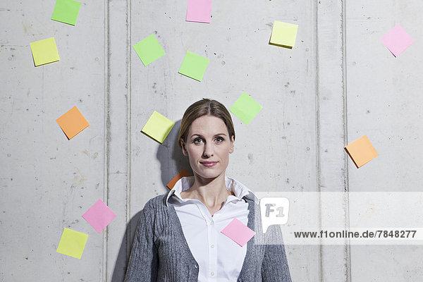 Deutschland  Nordrhein-Westfalen  Köln  Portrait einer Geschäftsfrau mit Haftnotizen