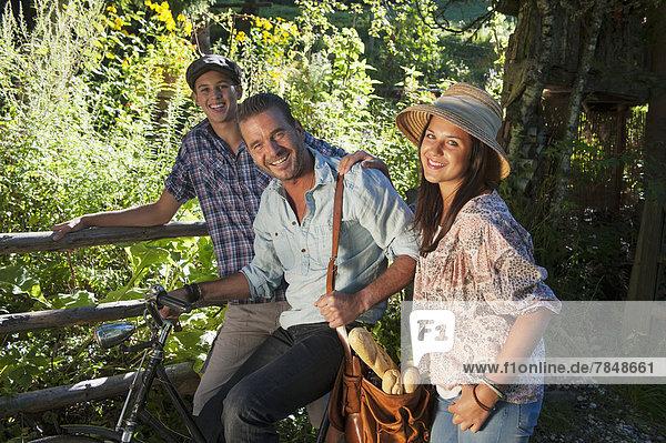 Österreich  Salzburg  Porträt der Familie im Garten  lächelnd