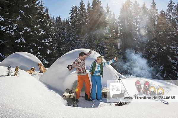 Österreich  Salzburg  Pärchen mit Spaß vor dem Iglu