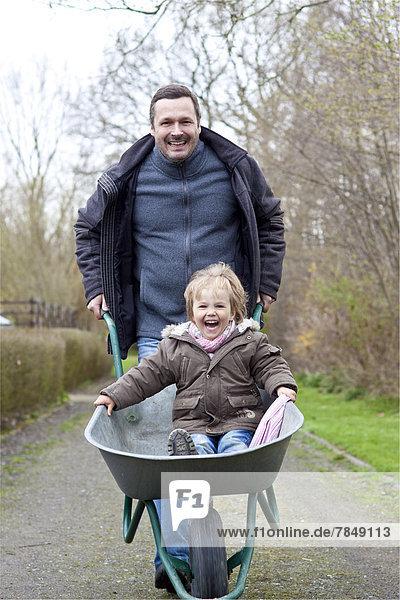 Deutschland  Vater schiebt Tochter auf Schubkarre  lächelnd