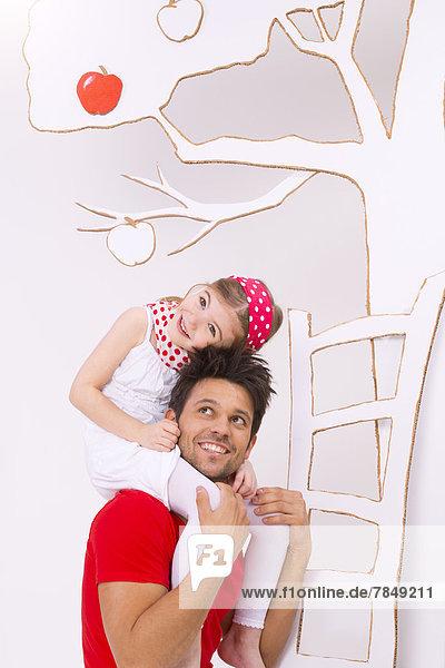 Mädchen sitzt auf der Schulter des Vaters und versucht  Apfel vom Baum zu pflücken  lächelnd
