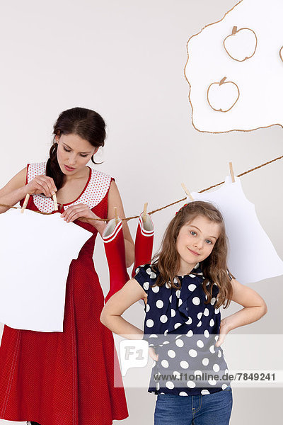 Mother and daughter hanging on laundry  smiling