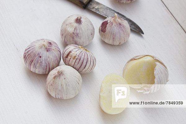 Garlics mit Messer auf Tisch  Nahaufnahme