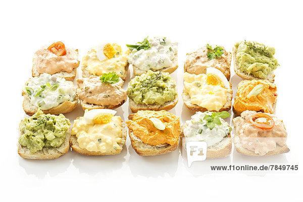 Verschiedene Brotaufstriche mit Thunfisch  Ei  Tomate  Mozarella  Schinken  grünen Zwiebeln  Liptauer und Avocado auf Ciabatta-Brot.