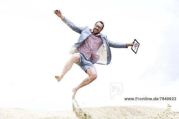 Deutschland  Bayern  Geschäftsmann springt auf Sand  lächelnd