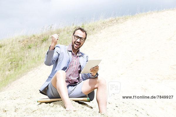Deutschland  Bayern  Portrait eines Geschäftsmannes auf Sand sitzend mit digitaler Tafel  lächelnd