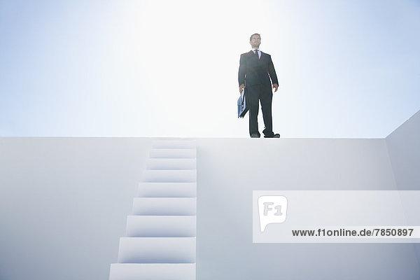 Geschäftsmann im schwarzen Anzug mit Aktentasche an der Wand stehend