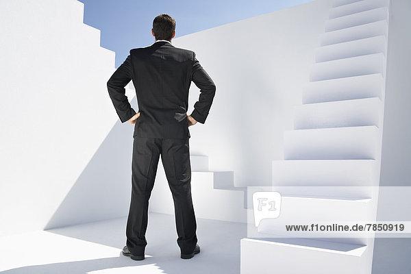 Geschäftsmann im schwarzen Anzug neben der Treppe stehend