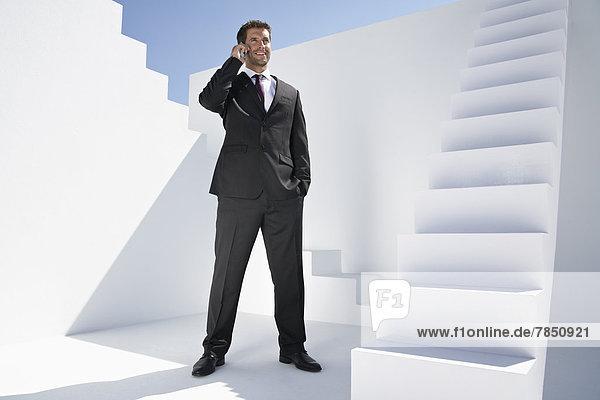 Geschäftsmann im schwarzen Anzug spricht auf dem Handy  lächelnd