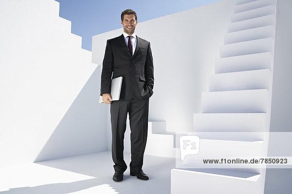 Geschäftsmann im schwarzen Anzug mit Laptop  lächelnd