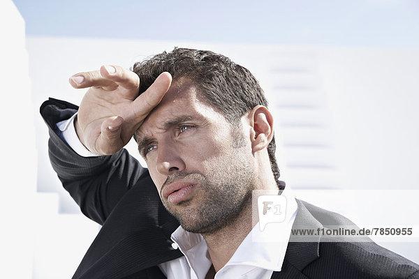 Müde Geschäftsmann in schwarzem Anzug  wegblickend