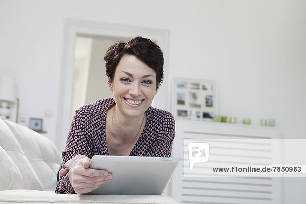 Porträt einer mittleren erwachsenen Frau mit digitalem Tablett auf der Couch  lächelnd