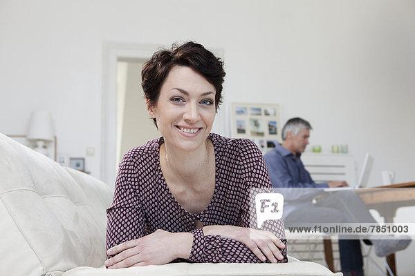 Porträt einer Frau  die sich auf das Sofa lehnt  während der Mann den Laptop im Hintergrund benutzt.