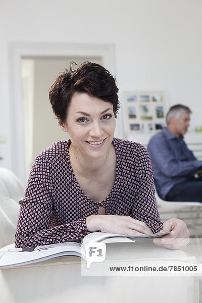 Porträt einer Frau  die im Hintergrund ein Magazin liest.