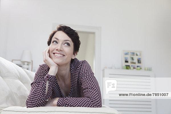 Mittlere erwachsene Frau entspannt auf der Couch  lächelnd
