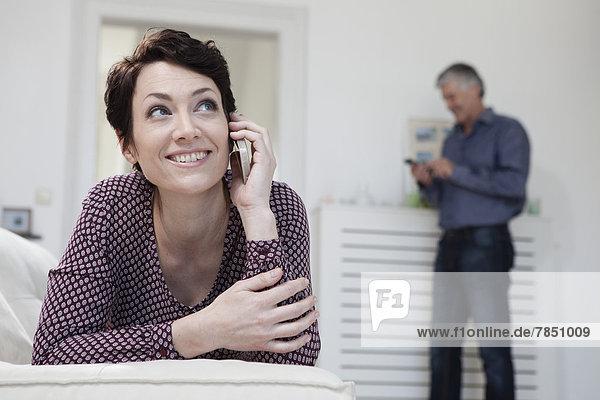 Frau spricht auf dem Handy  während Mann im Hintergrund