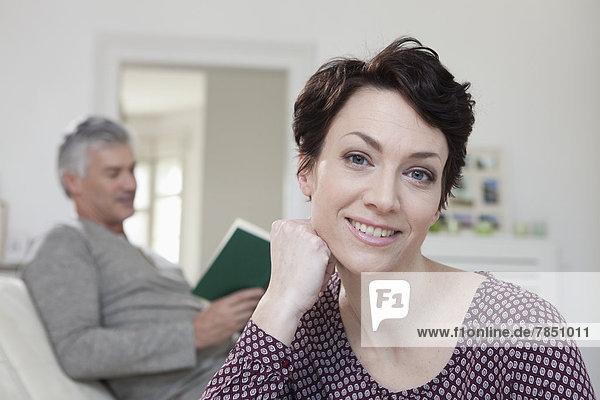 Porträt einer lächelnden Frau beim Lesen eines Buches im Hintergrund
