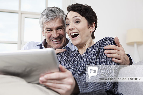 Deutschland  Bayern  München  Paar mit digitalem Tablett zu Hause  lächelnd