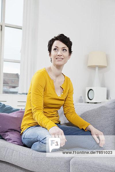 Mittlere erwachsene Frau auf der Couch sitzend  lächelnd