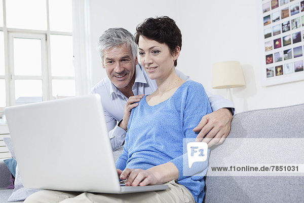 Germany  Bavaria  Munich  Couple using laptop at home  smiling