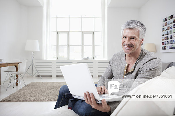 Portrait of mature man using laptop on couch  smiling