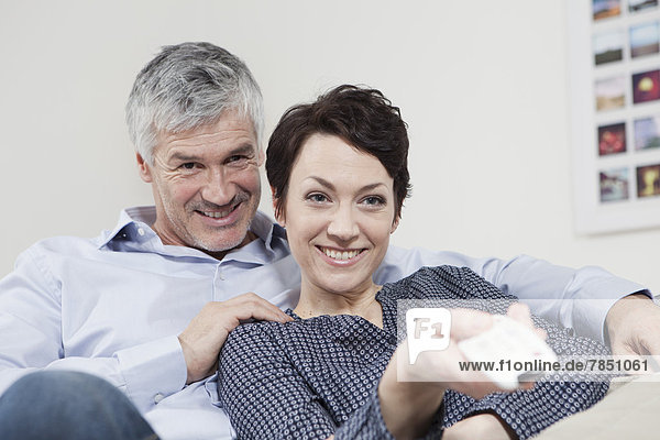 Germany  Bavaria  Munich  Couple changing channels with remote control  smiling