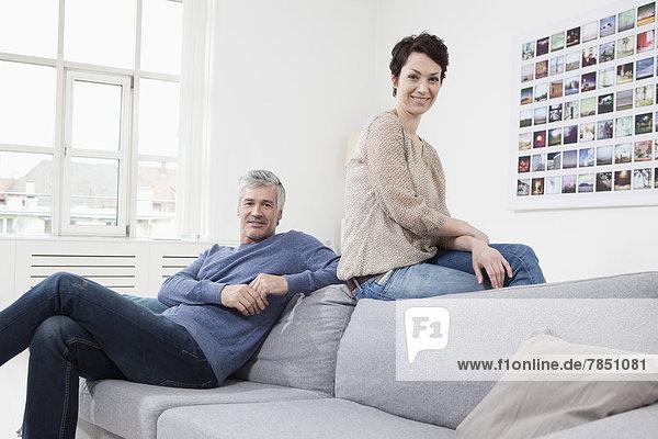 Deutschland  Bayern  München  Paar auf Sofa sitzend  lächelnd