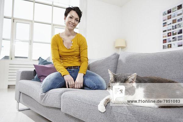 Mittlere erwachsene Frau mit Katze auf der Couch  lächelnd