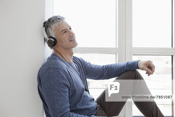 Mature man sitting at window with music  smiling