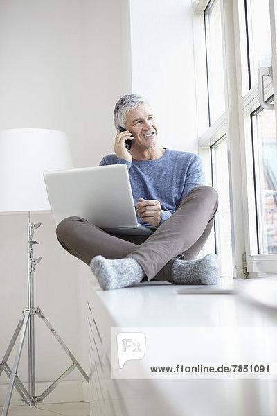 Erwachsener Mann spricht auf dem Handy und mit dem Laptop  lächelnd