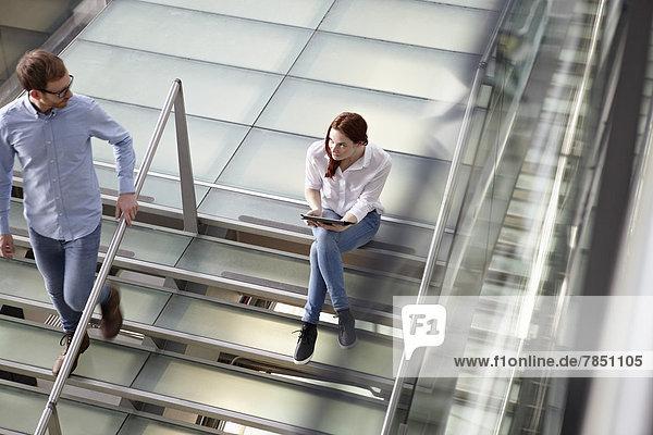 Junge Frauen mit Tablette  während der Mann die Treppe hinuntergeht.