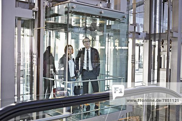 Junge Frau und reifer Mann in der Rolltreppe am Flughafen