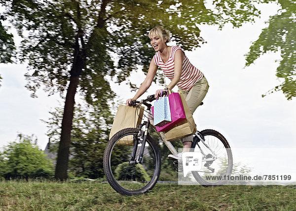 Junge Frau auf dem Fahrrad mit Einkaufstaschen
