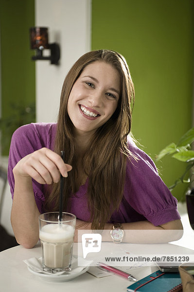 Portrait of young woman enjoying coffee in cafe  smiling