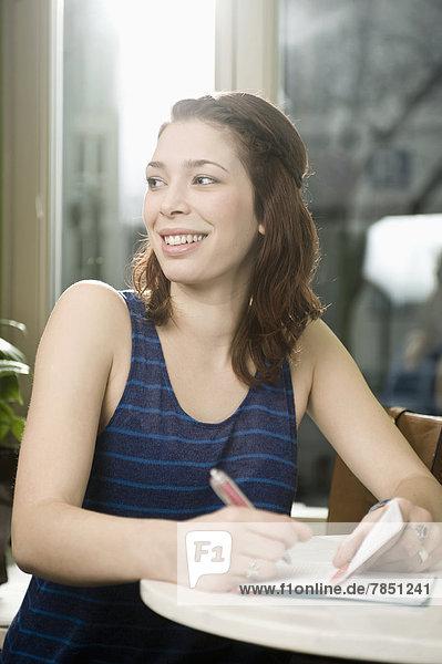 Junge Frau schreibt in Tagebuch  lächelnd