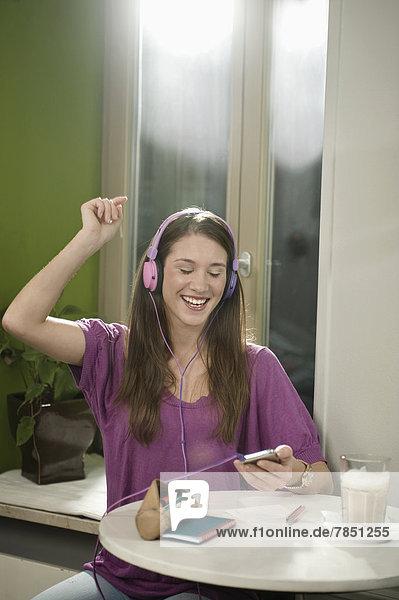 Junge Frau beim Musikhören im Café  lächelnd