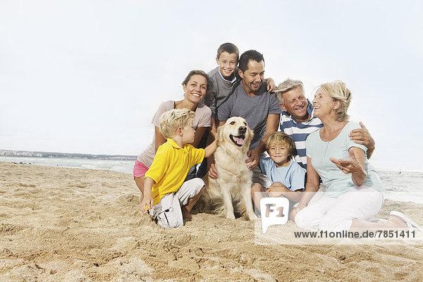Spain  Family sitting on beach at Palma de Mallorca  smiling
