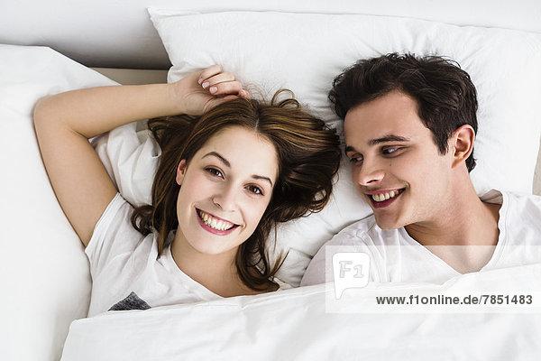 Junges Paar auf dem Bett liegend  lächelnd