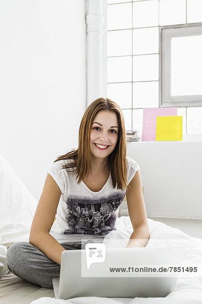 Portrait einer jungen Frau am Laptop  lächelnd