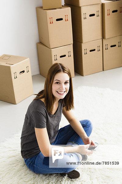 Porträt einer jungen Frau mit dem Handy  lächelnd