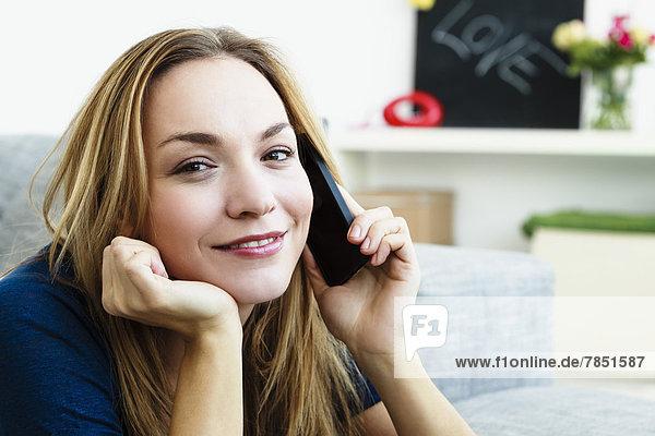 Porträt einer jungen Frau  die auf dem Handy spricht  lächelnd