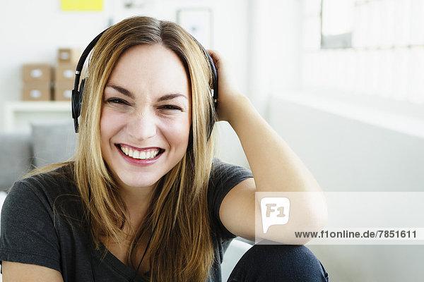 Porträt einer jungen Frau  die Musik hört  lächelnd