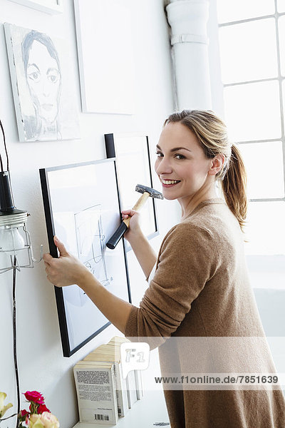 Portrait of young woman holding picture frame in front of wall  smiling