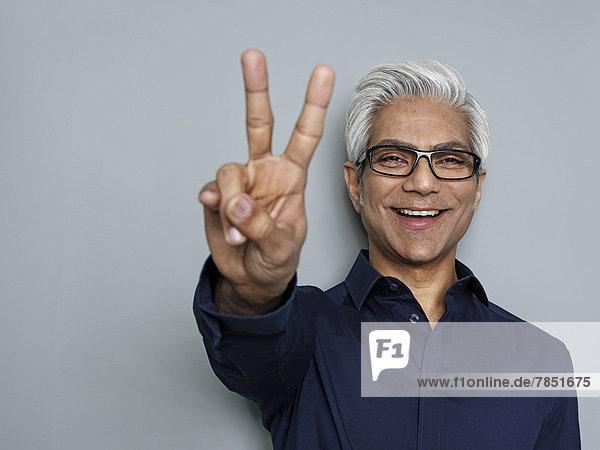 Geschäftsmann gestikuliert Friedenszeichen  lächelnd