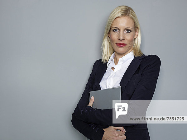 Porträt einer Geschäftsfrau mit Mappe  lächelnd