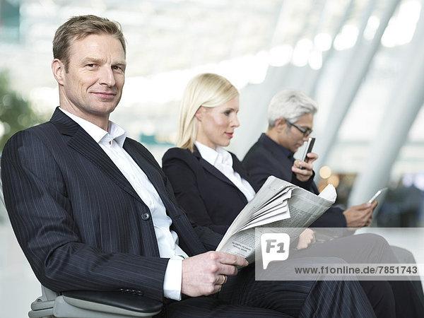 Geschäftsleute  die am Flughafen warten.