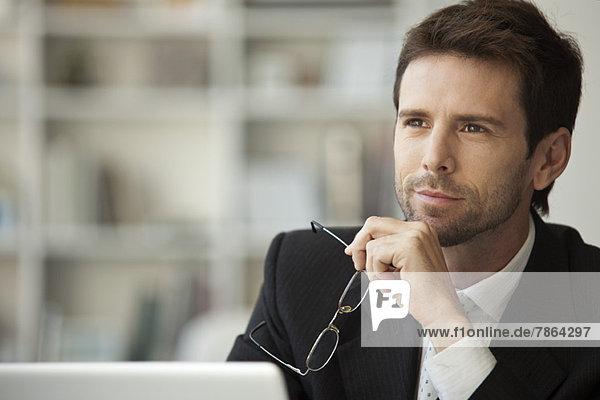 Geschäftsmann schaut in Gedanken weg  Brille in der Hand