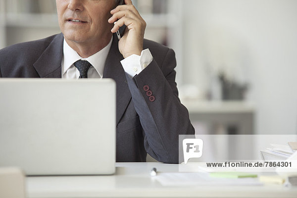 Businessman talking on cell phone and using laptop computer  cropped